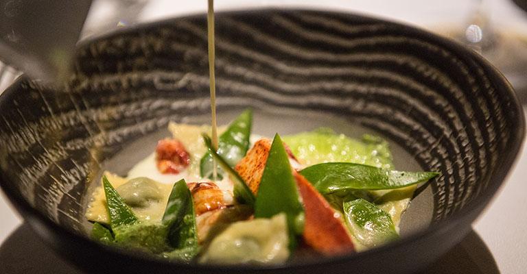 médaillon de homard, accompagné de ravioles d'épinard dans un bouillon de gruyère